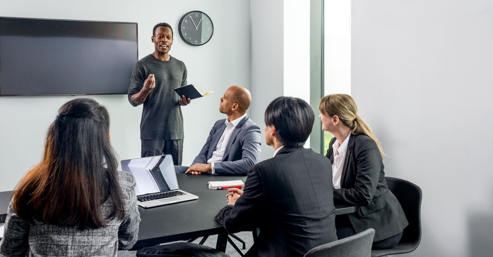 IELTS for work is an English Test that helps people to work worldwide. This picture shows people form different cultures in a meeting room discussing a topic.